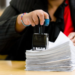 A woman stamps multiple documents